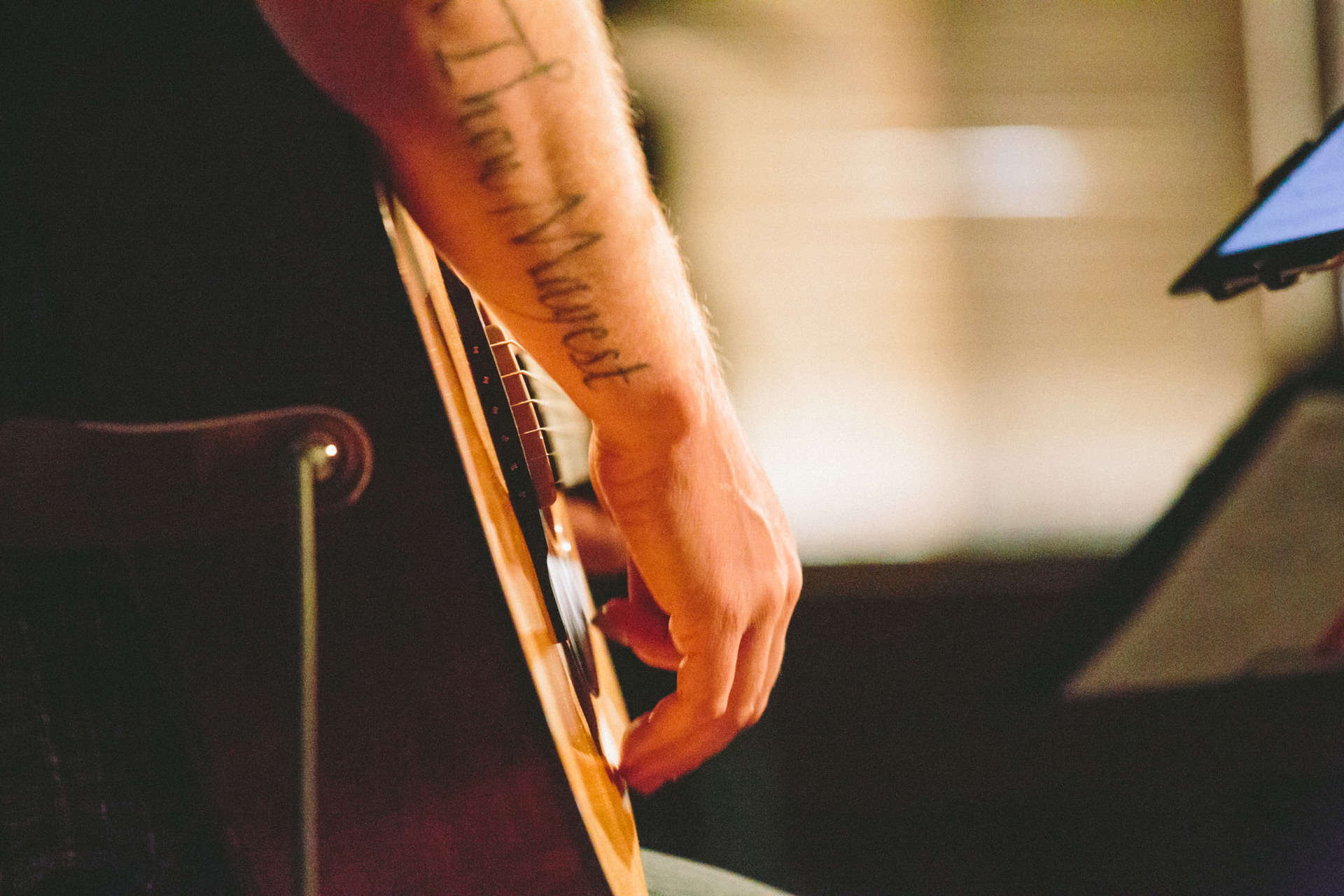 worship leader with arm tattoo playing guitar
