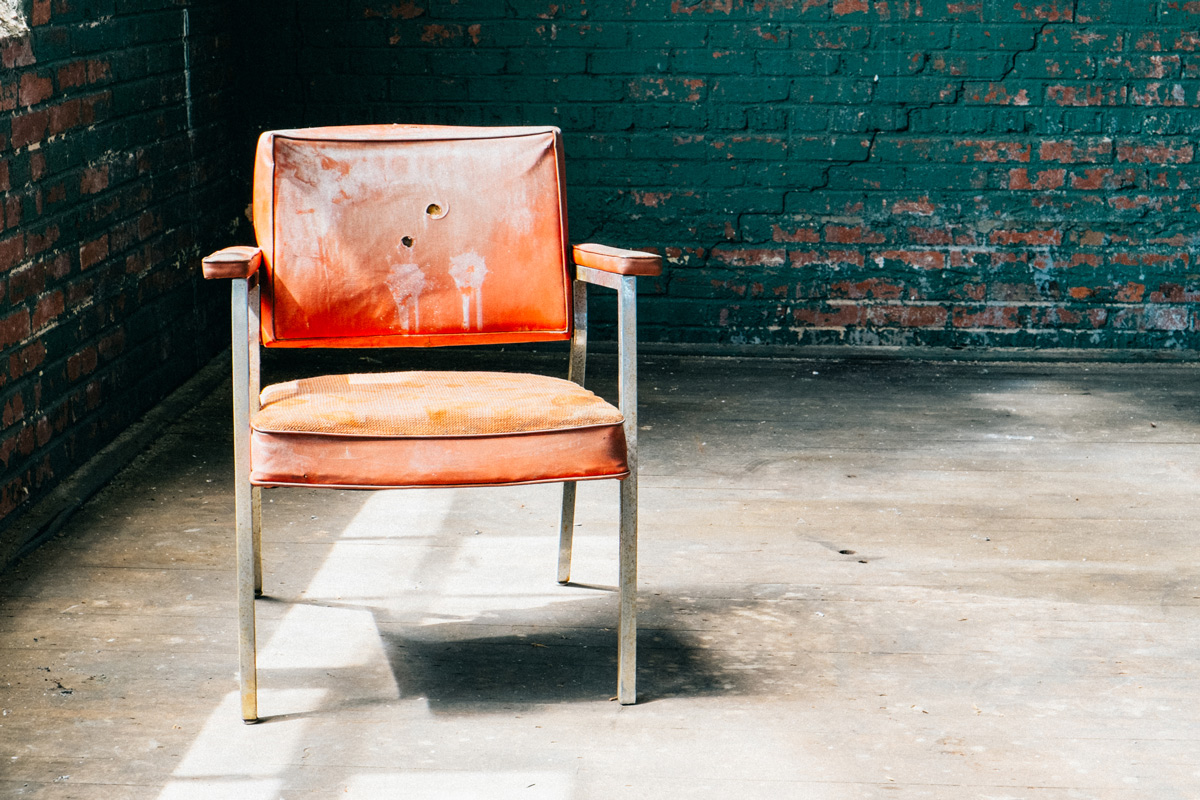 red chair in middle of grungy brick room