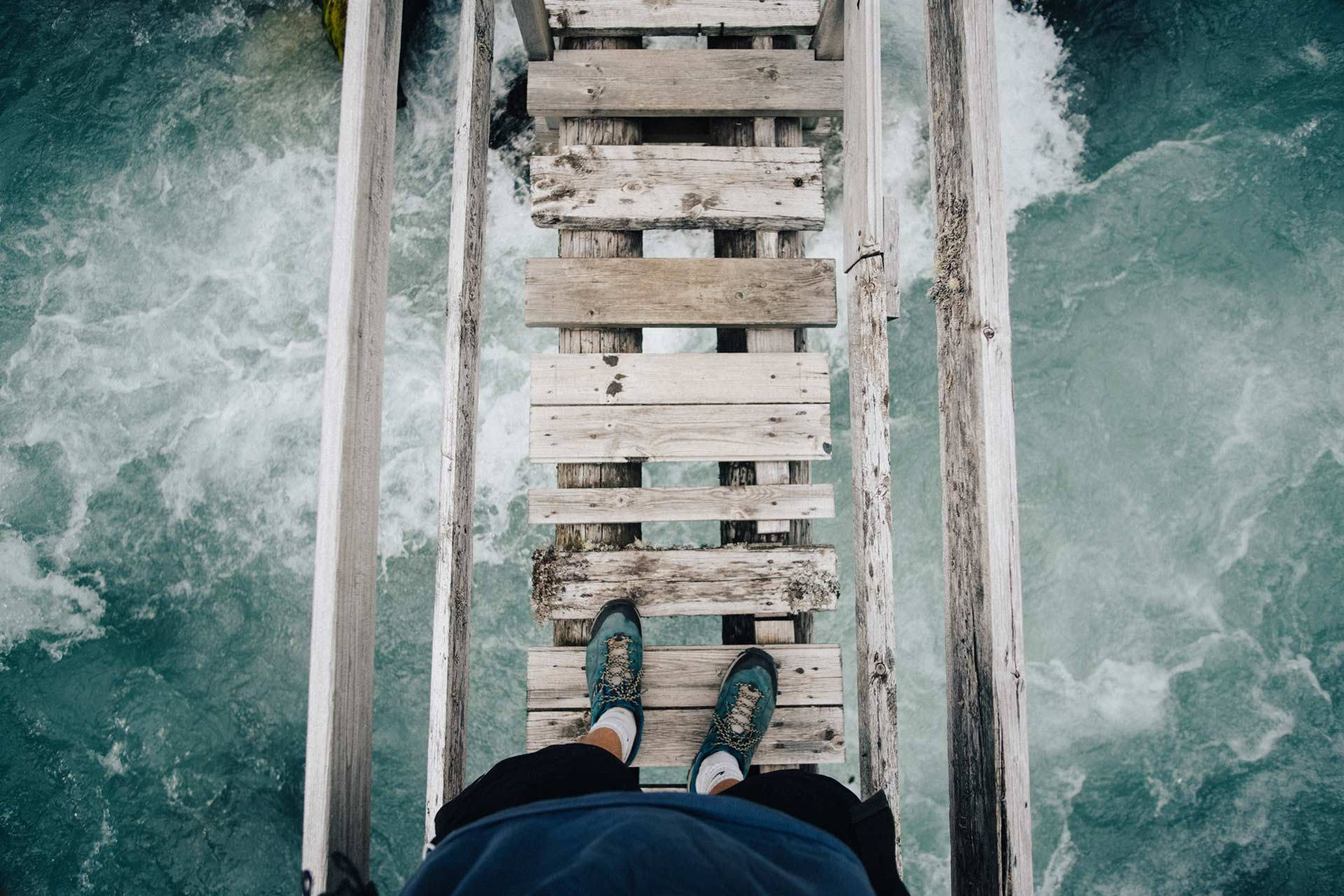 courage walking across narrow wooden bridge